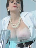 Mature blond nurse puts on latex gloves and plays with her massive ripe kahunas