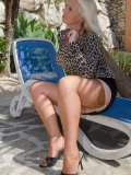 Busty oldie enjoys good time showing her nylon-clad legs and pussy in deckchair