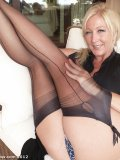 Swanky older lady pulls her skirt up playfully to show her stockings on garters