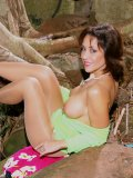 Gorgeous older lady in shiny pantyhose poses naked next to a waterfall in Hawaii