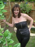 Exhibitionist MILF showing off her classy rack among the trees in her garden