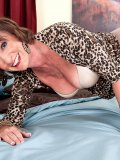 Smoking hot grandma bares it all for the camera before laying down in bed