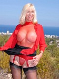 Gorgeous mature milf posing in a stunning red lingerie that flaunts her big tits