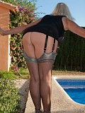 Wild mature housewife posing by the pool in super hot silver stockings