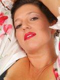 Mature lady lies down on the bed with the long dildo in her hand! What is she up to?