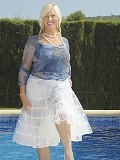 Beautiful mature housewife posing by the pool in a see through white skirt
