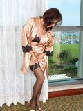 Horny mature housewife posing by the window in her sexy black lingerie