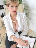 Mature business lady poses by her table with her large heavy jugs almost bare