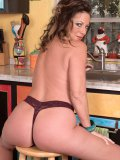Hot brunette housewife bends over and gets playfully horny in her kitchen