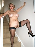 Ravishing blonde milf posing in a satin dress wearing nothing but a pair of stockings underneath