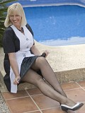 Sassy blonde milfSandy loves to tease posing by the pool in seductive stockings