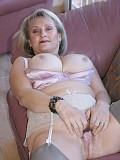 Sexy pictures of a mature busty blonde fingering her juicy pussy on the sofa