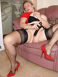 Frisky mature milf loves to pose in red high heels and stockings with her legs spread wide