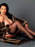 Sexy brunette milf posing in a fur coat and revealing her furry pussy