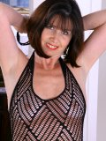 This mature babe looks awesome in her black bodystocking and out of it as well