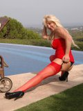 Mum in red top and stockings poses by the pool sliding out of her panties slowly
