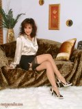 Sassy mature brunette posing on the bed in her black stockings and playing with herself