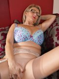 Big-tittied MILF spreads the shaven hole locked in between her nylon-clad hips