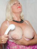 Big-tittied nylon-loving mature drenches her tits and nylon-clad legs with water
