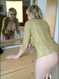 Stunning mature beauty with big breasts scrutinizes her naked body in the mirror