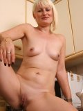 Blond momma with punky hairstyle demonstrates her clit piercing in the kitchen