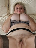 Hot blonde milf enjoys posing in black nylons while she squeezes her gigantic boobs