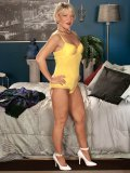 Seductive lady strips off her yellow bodysuit and then poses flirtatiously for more sexual fun.