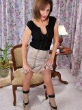 Hot brunette milf posing in sexy boots and flashing her amazing black stockings