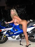 Gorgeous blonde babe strips naked and spreads her legs open while riding a bike