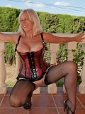 Naughty blonde mature milf reveals her massive tits in a hot corset and stockings