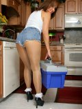 Hot brunette milf babe posing in the kitchen in the tiniest shorts that show her juicy pussy lips