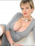 MILF posing in opaque white knee-high stockings and with her heavy melons bare