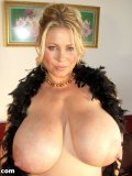 Samantha 38G is here to show off her enormous juggies wrapped in a feathery boa