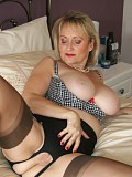 Slutty blonde milf babe reveals her juicy pussy posing on the bed in stockings