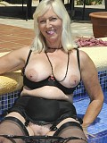 Gorgeous blonde milf loves to pose just in her stockings by the pool