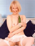 Joyful blond granny grabs a totally enormous cucumber and stuffs it into herself