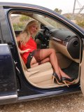 Mature nylon model shows her stockings and panties next to a cool-ass large SUV