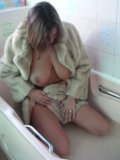 Mature lady with oversized boobs enjoys the tickle of soft fur in her bathroom