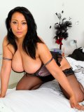 Latin cougar lets her big tits pop out from under her lingerie and toys herself