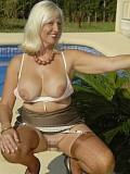 Slutty blonde milf can't keep her hands off of her incredibly big bare boobs