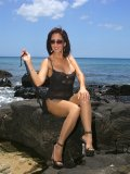 Amazing pictures of the hot brunette milf posing in sexy nylons on the beach