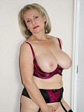 Stunning pictures of a sexy blonde milf posing in silky lingerie and playing with her massive jugs