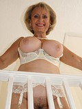 Busty mature milf exposes her huge melons and plays with her hairy pussy on the staircase
