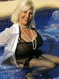 Ravishing slutty mature blonde posing in seductive black lingerie by the pool