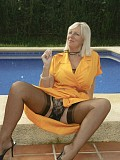 Naughty busty Sandy getting undressed by the pool to flaunt her killer jugs