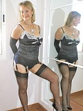 Naughty blonde milf posing in sexy black stockings while fingering herself