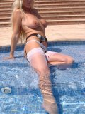 Hot blond mature tries the water in the pool with the tip of her nylon-clad toes