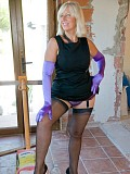 Glamorous pics of a mature blond Sandy posing in purple lingerie and stockings and playing with herself