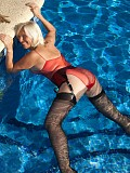 Beautiful blonde Sandy swims in the pool in sexy black stockings that show off her killer legs