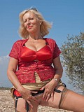Hot pictures of a gorgeous blonde milf revealing her massive tits outdoors